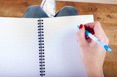 A mulher entrega a escrita para baixo no livro de nota Fotografia de Stock