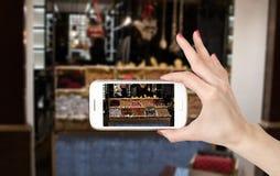 A mulher entrega a foto em linha com um telefone esperto Imagem de Stock
