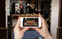 A mulher entrega a foto em linha com um telefone esperto Foto de Stock