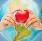 A mulher entrega guardar o coração vermelho sobre o globo da terra Imagens de Stock Royalty Free