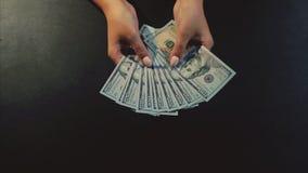 A mulher entrega mostrar um fã das notas de dólar no fundo preto video estoque