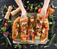 A mulher entrega o alcance para a pizza deliciosa grande do cogumelo decorada Imagem de Stock Royalty Free