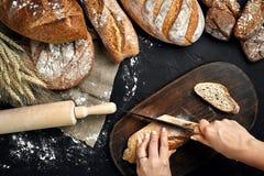 A mulher entrega o corte de um naco de pão na placa de madeira rústica, com orelhas do trigo e faca, vista superior Imagens de Stock