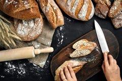 A mulher entrega o corte de um naco de pão na placa de madeira rústica, com orelhas do trigo e faca, vista superior Fotos de Stock