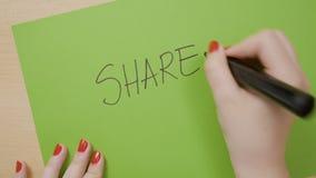 A mulher entrega a parte da escrita em maiúsculo e sublinhando a em um papel verde usando um marcador preto - filme
