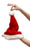 A mulher entrega prender o chapéu de Santa foto de stock royalty free