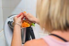 A mulher entrega a preparação do puré da abóbora na máquina do cozinheiro fotografia de stock