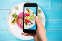 A mulher entrega a tomada de peixes da foto com o vegetal misturado com smartphone Imagem de Stock Royalty Free