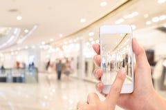 A mulher entrega a tomada de uma imagem com um telefone esperto no shopping imagens de stock royalty free