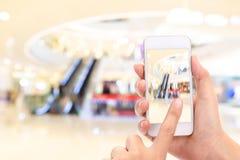 A mulher entrega a tomada de uma imagem com um telefone esperto no shopping com imagem borrada da loja de roupa fotografia de stock royalty free