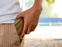A mulher entrou o móbil no bolso da calças Foto de Stock