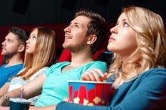 Mulher entusiasmado com pipoca no cinema imagem de stock royalty free