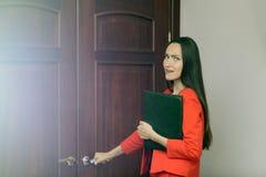 Mulher entusiasmado e amedrontada em um terno vermelho com os originais à disposição que batem na porta ao chefe Foto de Stock