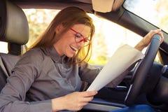 Mulher entusiasmado em papéis da leitura do carro imagens de stock royalty free