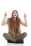 A mulher entusiasmado está sentando-se em um assoalho, na vista acima e em apontar Imagens de Stock Royalty Free