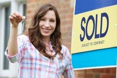 Mulher entusiasmado fora da casa nova que guarda chaves imagens de stock royalty free