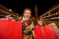 Mulher entusiasmado no revestimento do inverno que mostra sacos de compras em Veneza Fotos de Stock Royalty Free