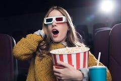 mulher entusiasmado nos vidros 3d com a cesta grande do filme de observação da pipoca Fotos de Stock