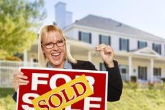 Mulher entusiasmado que guarda chaves da casa e o sinal vendido de Real Estate Imagem de Stock Royalty Free