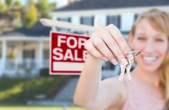 Mulher entusiasmado que guarda chaves da casa e para o sinal de Real Estate da venda mim imagens de stock