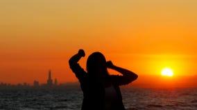 Mulher entusiasmado que salta no por do sol que comemora o sucesso