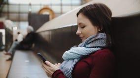 Mulher entusiasmado que texting no smartphone que senta-se no banco de mármore no estação de caminhos de ferro vídeos de arquivo