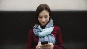 Mulher entusiasmado que texting no smartphone que senta-se no banco de mármore na estação de metro filme