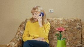 A mulher envelheceu a fala em um telefone celular no sofá em casa Movendo a câmera vídeos de arquivo