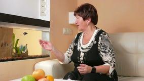 A mulher envelheceu o descanso em casa olhando peixes em um aquário Toca no vidro e na fala com peixes Assento na vídeos de arquivo