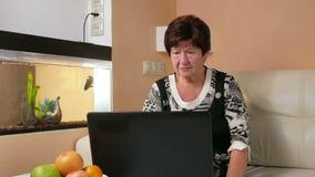 A mulher envelheceu o trabalho no portátil em casa no sofá Olha fixamente na tela e pressiona a chave Ao lado dos peixes da nataç vídeos de arquivo