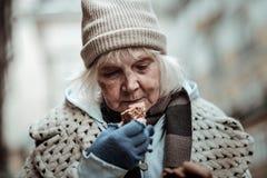 Mulher envelhecida agradável que olha o pão foto de stock