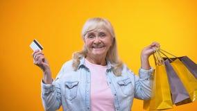 Mulher envelhecida alegre que mostra sacos de compras e cartão de banco, serviços para aposentados filme