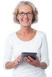Mulher envelhecida com dispositivo de almofada do toque Imagem de Stock