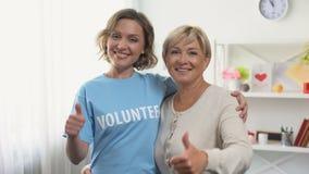 A mulher envelhecida e o voluntário fêmea que mostram os polegares acima do aperto, ajudam povos aposentados video estoque