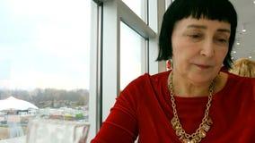 A mulher envelhecida elegante, afiliação étnica caucasiano, bebe a água do vidro transparente video estoque