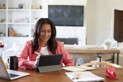 Mulher envelhecida média de sorriso que senta-se em um desenho da tabela em um tablet pc com um estilete, vista dianteira fotografia de stock royalty free