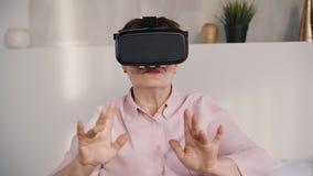Mulher envelhecida média em vidros de Google no capacete do vr