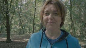 A mulher envelhecida média está na floresta e nos tunrs com câmera e olhares filme