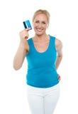 Mulher envelhecida média na moda que mostra o cartão de crédito fotografia de stock royalty free