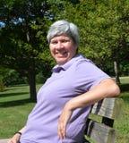 Mulher envelhecida média no sorriso do banco Fotografia de Stock Royalty Free