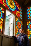 Mulher envelhecida média que olha durante todo a janela com vitral multi-colorido, Tbilisi velho, Geórgia, em janeiro de 2019 imagens de stock royalty free