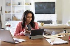 Mulher envelhecida média que senta-se em uma leitura da tabela usando um tablet pc, guardando um copo, vista dianteira foto de stock
