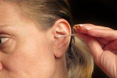 Mulher envelhecida m?dia que limpa sua orelha com o cotonete ou a vara de algod?o Close up do procedimento rotineiro dos cuidados fotografia de stock royalty free