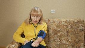 A mulher envelhecida mede a pressão de sua própria casa no sofá Escuta o pulso através do sphygmomanometer filme