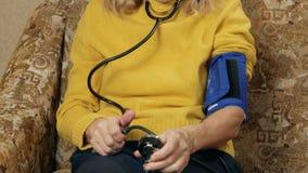 A mulher envelhecida mede a pressão de sua própria casa no sofá Escuta o pulso através do sphygmomanometer video estoque
