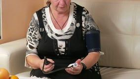 A mulher envelhecida mede a pressão sanguínea em casa Veste um punho e o testemunho do dispositivo médico olha proximamente filme