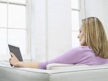 Mulher envelhecida meio com o portátil no sofá imagens de stock royalty free