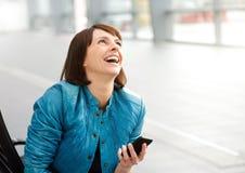 Mulher envelhecida meio de sorriso com telefone celular Fotografia de Stock Royalty Free