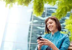 Mulher envelhecida meio de sorriso que usa o telefone celular fora Foto de Stock Royalty Free