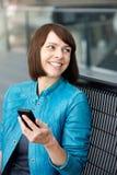 Mulher envelhecida meio que sorri com telefone celular Fotografia de Stock
